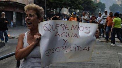 Una mujer enseña una pancarta durante una protesta en Venezuela