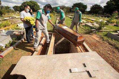 Empleados preparan a víctimas de COVID-19 para ser enterrados en el cementerio de Campo da Esperança, en Brasilia (Brasil). EFE/Joédson Alves
