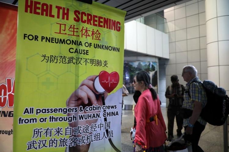 Los pasajeros pasan por una pancarta sobre la neumonía de Wuhan en el punto de detección térmica en la terminal internacional de llegadas del aeropuerto internacional de Kuala Lumpur en Sepang, Malasia, el 21 de enero de 2020. (REUTERS / Lim Huey Teng)