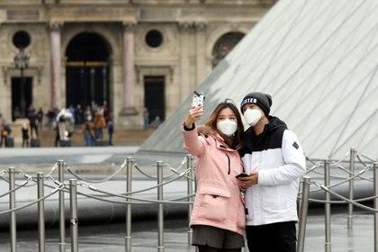 Una pareja se toma una selfie con barbijos delante del Museo del Louvre, en  París -  REUTERS/Charles Platiau