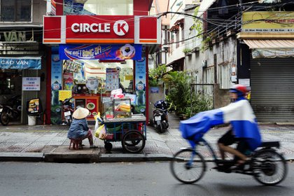 A fruit vendor sits waiting for customers at her cart outside a Circle K store in Ho Chi Minh City, Vietnam, on Wednesday, June 20, 2018. For decades, Vietnamese have shopped, snacked and hung out at the country's traditional markets: colorful, chaotic mazes of open air stalls where vendors hawk everything from fruits and vegetables, to sandwiches and sodas to the odd clucking chicken. Now a full-scale convenience-store flood is coming. Circle K, a chain owned by Canada's Alimentation Couche-Tard Inc., led the way for foreign convenience stores 10 years ago. Photographer: Maika Elan/Bloomberg