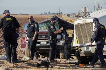 Miembros de los Equipos multidisciplinarios de investigación de accidentes (MAIT) inspeccionan la escena de una colisión entre un vehículo utilitario deportivo (SUV) y un camión cerca de Holtville, California, EE. UU., 2 de marzo de 2021. REUTERS / Bing Guan