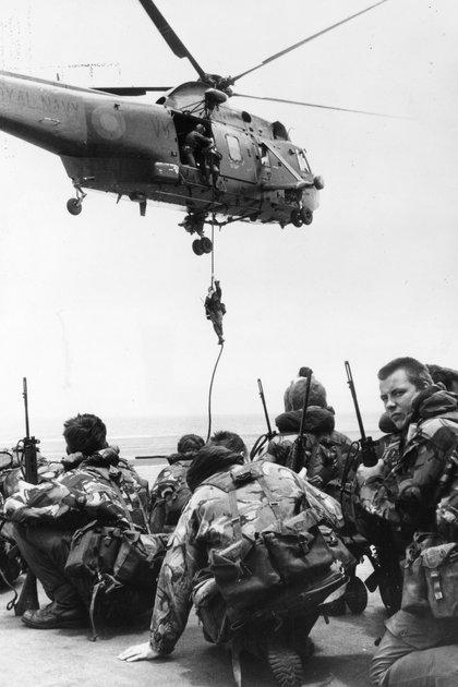 Soldados de la Marina Real esperando a ser transportados por un helicóptero Westland Sea King Waiting del las fuerzas británicas (Fox Photos/Getty Images)