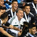 Argentine former footballer and Mexico's manager Gerardo Martino holds the gold cup and celebrates with Mexico players after beating the US during the 2019 Concacaf Gold Cup final football match between USA and Mexico on July 7, 2019 at Soldier Field stadium in Chicago, Illinois. - Mexico defeated the US 1-0 (Photo by TIMOTHY A. CLARY / AFP)