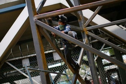 Un trabajador de la construcción con un pañuelo en la boca trabaja según el protocolo contra covid-19 (Reuters)