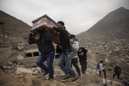 Parientes de un hombre de 35 años cargan su ataúd en las afueras de Lima, Perú (AP)