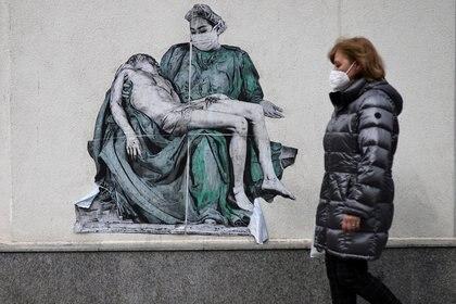 """Una mujer pasa frente a un mural que replica """"La Piedad"""" de Miguel Ángel cerca de un centro de vacunación en el hospital Pirogov en Sofia, Bulgaria (REUTERS/Stoyan Nenov)"""