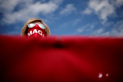 A supporter of U.S. President Donald Trump wears a MAGA (Make America Great Again) protective face mask during a campaign rally at Pitt-Greenville Airport in Greenville, North Carolina, U.S., October 15, 2020. REUTERS/Carlos Barria