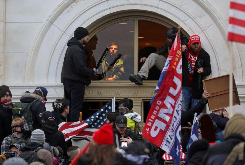 Imagen de archivo de una turba de partidarios del entonces presidente de Estados Unidos, Donald Trump, escalando por una ventana que rompieron para entrar al Capitolio en Washington, Estados Unidos. 6 de enero, 2021. REUTERS/Leah Millis/Archiv