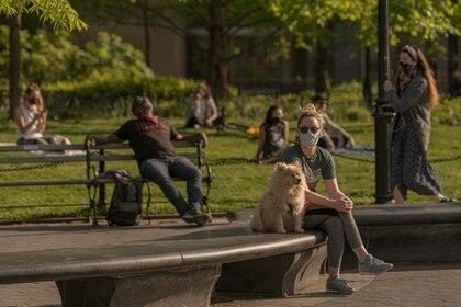Personas descansando, algunas con cubrebocas, en el Washington Square Park en Nueva York, el 14 de mayo de 2020. (Jeenah Moon/The New York Times)