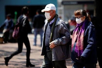 Personas adultas caminan usando tapabocas como medida previentiva para evitar el contagio del coronavirus en una calle de Bogotá, Colombia, 17 de marzo, 2020. REUTERS/Leonardo Muñoz. NO VENTA NO ARCHIVO