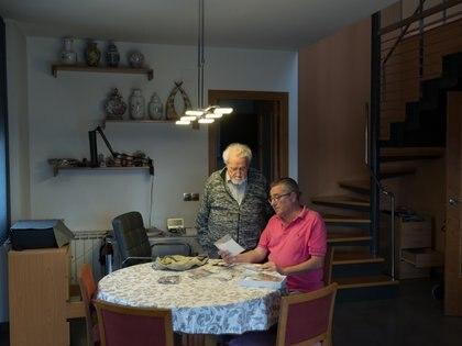 Andreu Canet mira viejas fotografías con su hijo Andreu, en su casa de Cardedeu, España (Samuel Aranda/The New York Times)