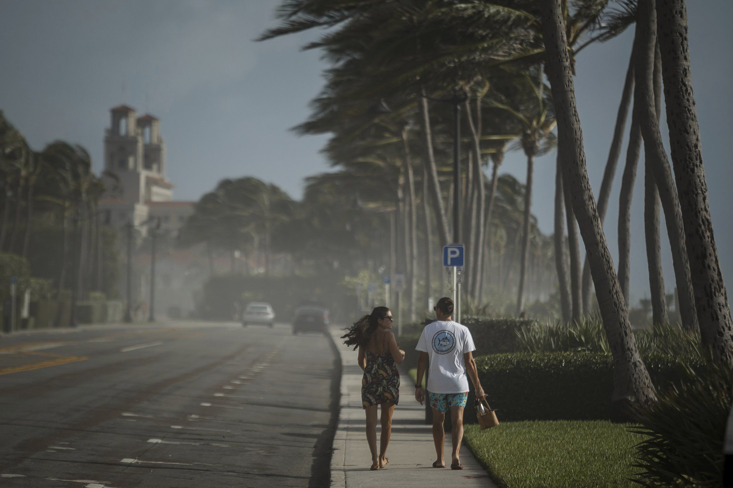 Sea spray, sand and winds sweep across South Ocean Boulevard in Palm Beach, Fla., as Palm Beach County readies for Hurricane Isaias on Saturday, Aug. 1, 2020.   Isaias snapped trees and knocked out power as it blew through the Bahamas on Saturday and churned toward the Florida coast, where it is threatening to complicate efforts to contain the coronavirus in a hot spot. (Thomas Cordy/The Palm Beach Post via AP)
