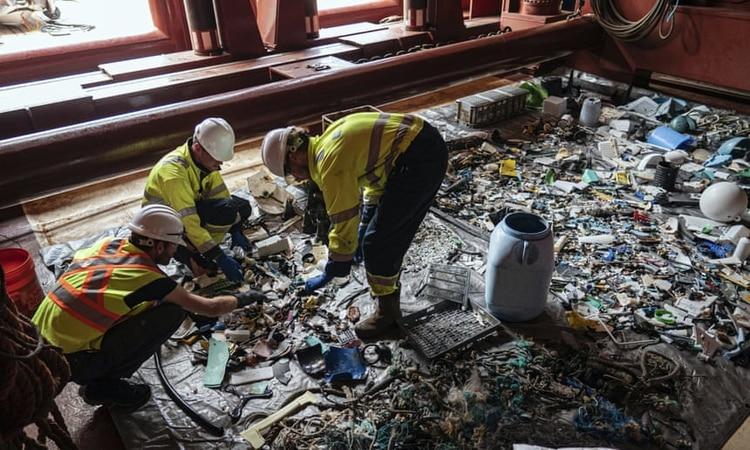 Los miembros de la tripulación clasifican a través de plástico a bordo de una embarcación de apoyo en el Pacífico. Fotografía: AP