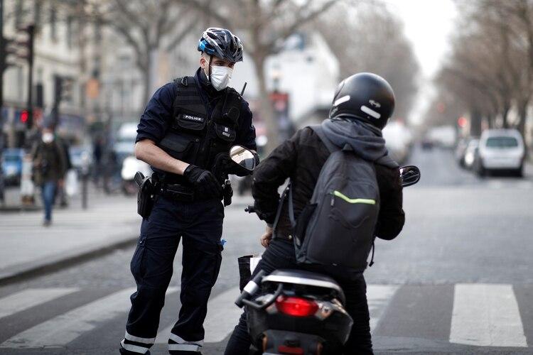 Un policía francés constata la circulación de un motoclista en París mientras la pandemia de coronavirus se expande en Europa REUTERS/Benoit Tessier