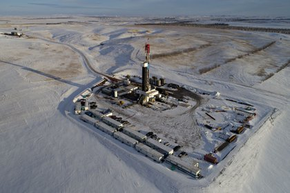 A Unit Drilling Co. rig stands in the Bakken Formation in this aerial photograph outside Watford City, North Dakota, U.S., on Friday, March 9, 2018. When oil sold for $100 a barrel, many oil towns dotting the nation's shale basins grew faster than its infrastructure and services could handle. Since 2015, as oil prices floundered, Williston has added new roads, including a truck route around the city, two new fire stations, expanded the landfill, opened a new waste water treatment plant and started work on an airport relocation and expansion project.