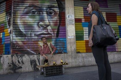 Un vendedor callejero ofrece bananas frente a una pintura con la imagen del líder independentista venezolano Simón Bolívar en Caracas, Venezuela, el martes 16 de julio de 2019. (AP Foto/Rodrigo Abd)