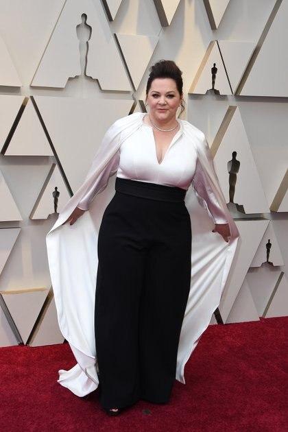 Melissa McCarthy eligió para los Oscars una monoprenda en color blanco y negro que desde el top caía una capa en seda. Completó el look con gargantilla plateada y cabello recogido