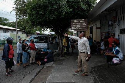 Un pastor evangélico realiza una prédica a familiares de personas ingresadas por COVID-19, afuera del Hospital Alemán Nicaragüense en Managua (Nicaragua). EFE/ Carlos Herrera