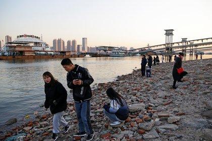 Personas caminan por la vera del río en Wuhan, China. Foto: REUTERS/Tingshu Wang