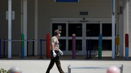 A Miami-Dade County police officer walks outside the passengers terminal where the Coral Princess ship, of Princess Cruises fleet, with patients affected by coronavirus disease (COVID-19), is docked at Miami Port, in Miami, Florida, U.S., April 4, 2020. REUTERS/Marco Bello