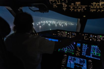Imagen desde la cabina del Boeing 787de Enrique Piñeyro, comandado por él mismo (de espaldas en la foto). Lo que se ve a través del vidrio es la ciudad de pesqueros extranjeros. (Foto: Franco Fafasuli)