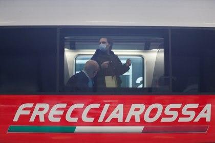 """Un ferroviere e un passeggero su un treno diretto """"COVID è gratuito"""" Da Roma a Milano.  Il 16 aprile 2021.  REUTERS / Yara Nardi"""