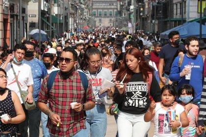 Personas caminan por calles del Centro Histórico, con las mínimas medidas de seguridad por la COVID-19, hoy en Ciudad de México (México). México reportó 261 nuevas muertes por la COVID-19 en las últimas 24 horas para llegar a un total de 217.168 decesos, informó este sábado la Secretaría de Salud. EFE/Mario Guzmán