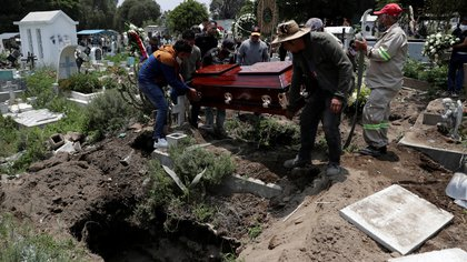 Relatives and friends carry the coffin of a man, during his funeral at the local cemetery, as the coronavirus disease (COVID-19) outbreak continues in Mexico City, Mexico, August 6, 2020. REUTERS/Henry Romero