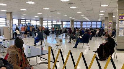 """Personas esperan su turno para vacunarse contra la covid-19 en el centro temporal habilitado en el """"Aviation High School"""", el 26 de febrero de 2021 en el distrito de Queens, Nueva York (EE.UU). EFE/Helen Cook/Archivo"""