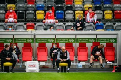 Uwe Roesler, entrenador del Fortuna Dusseldorf, el único sin mascarilla en el banquillo, que solo fue ocupado por sus auxiliares porque los suplentes se ubicaron en las gradas (REUTERS)
