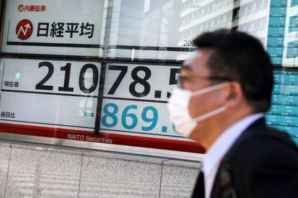 Una persona pasa frente a una pantalla con el índice Nikkei en Tokio (REUTERS/Athit Perawongmetha)