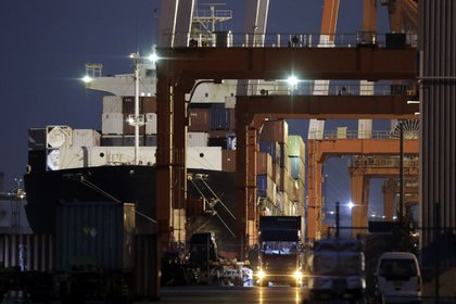 The YM Inauguration container ship berthed at a shipping terminal at night in Yokohama, Japan, on Monday, Dec. 14, 2020. Japan is scheduled to release trade balance figures on Dec. 16. Photographer: Kiyoshi Ota/Bloomberg