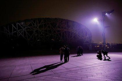 La gente se para frente al Estadio Nacional, también conocido como Nido de Pájaros, en Pekín, China