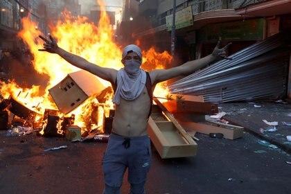 Un manifestante, frente a una barricada en llamas junto a una tienda saqueada durante una protesta contra el gobierno en Valparaíso, en Chile. 26 de noviembre de 2019. REUTERS/Goran Tomasevic