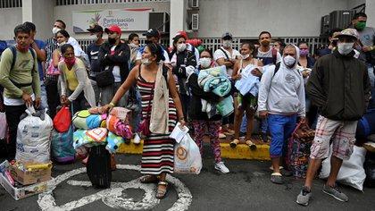 La despedida fue en medio del llanto de los que partían con sus ilusiones guardadas en maletas y bultos y de quienes se quedaban a la espera de poder viajar próximamente (Luis ROBAYO / AFP)