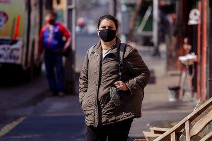 Fotografía que muestra una mujer con tapabocas mientras espera el transporte público en la zona del mercado 4 de Asunción (Paraguay). EFE/Nathalia Aguilar/Archivo