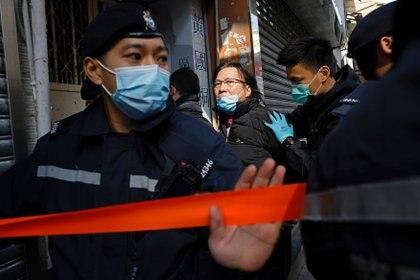 Daniel Wong Kwok-tung, un abogado que intentó ayudar a las 12 personas detenidas en China continental, es escoltado por la policía cuando regresa a su oficina en Hong Kong, China. REUTERS/Tyrone Siu