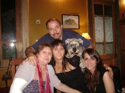 Dante Converti, con amigas. Detrás, un cuadro con su casa de Río Gallegos (Facebook)