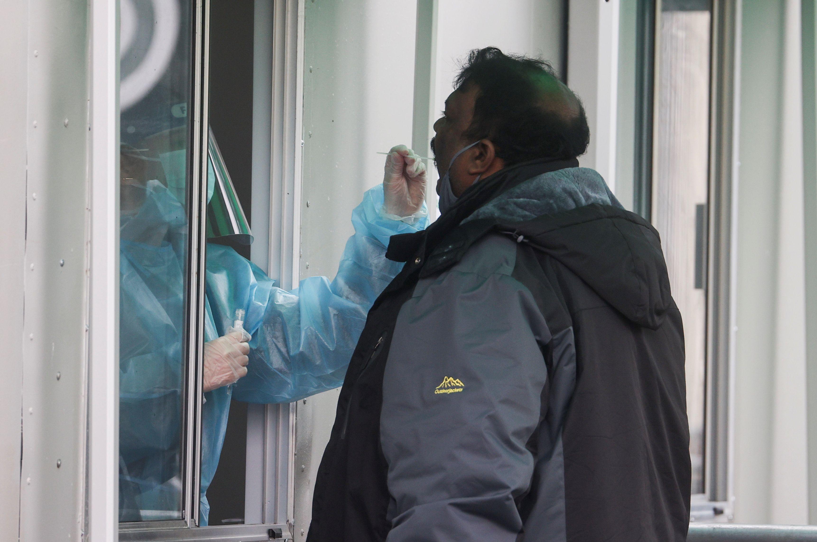 Un trabajador de la salud realiza una prueba PCR a un hombre para detectar la enfermedad del coronavirus (COVID-19), en un sitio de prueba móvil de COVID-19 en el aeropuerto de Heathrow, en Londres, Gran Bretaña, el 15 de febrero de 2021. REUTERS / Hannah McKay