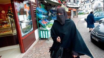 Una mujer marroquí de 32 años pasa por la puerta de una panadería en una calle de Le Mesnil-Saint-Denis, 38 kilómetros al sudoeste de París. La discusión por el velo es un debate recurrente en Francia. (AP)