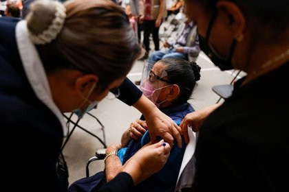 Un trabajador de la salud administra una dosis de la vacuna contra el COVID-19 de Sinovac a una adulta mayor, durante una vacunación masiva en Ecatepec, Estado de México. 22 de febrero de 2021. REUTERS / Carlos Jasso
