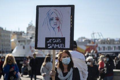 """Una persona sostiene un letrero que dice """"Yo soy Samuel"""" mientras la gente se reúne en el Vieux Port de Marsella el 18 de octubre de 2020 (Foto de Christophe SIMON / AFP)"""