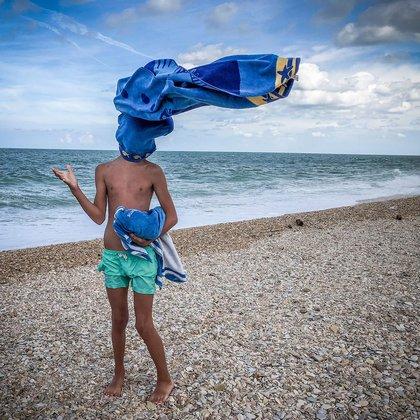 """Josien Van Geffen, Países Bajos. Mención en la categoría de """"Fotos tomadas con un smartphone"""".Civitanova, Italia. Un hombre lanzó la toalla hacia su hijo para ver cuán fuerte soplaba el viento (Josien Van Geffen/www.tpoty.com)"""