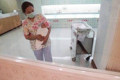 Una enfermera con una mascarilla protectora sostiene a un bebé recién nacido con un protector facial durante el brote de COVID-19 en el hospital Praram 9 en Bangkok, Tailandia, 9 de abril de 2020 (REUTERS/Athit Perawongmetha)