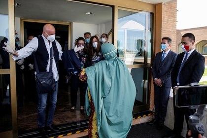 Silvia Romano es recibida por su padre, Enzo Romano, quien se prepara para abrazarla luego de estar secuestrada 18 meses en Somalía (Reuters)
