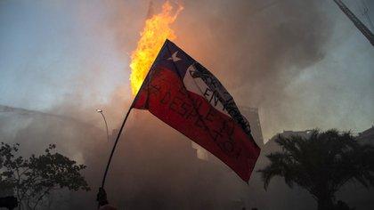 Un manifestante ondea una bandera chilena frente a la iglesia en llamas de Asunción, incendiada por los manifestantes, en la conmemoración del primer aniversario del levantamiento social en Chile, en Santiago, el 18 de octubre de 2020, mientras el país se prepara para un referéndum histórico.  (Photo by MARTIN BERNETTI / AFP)