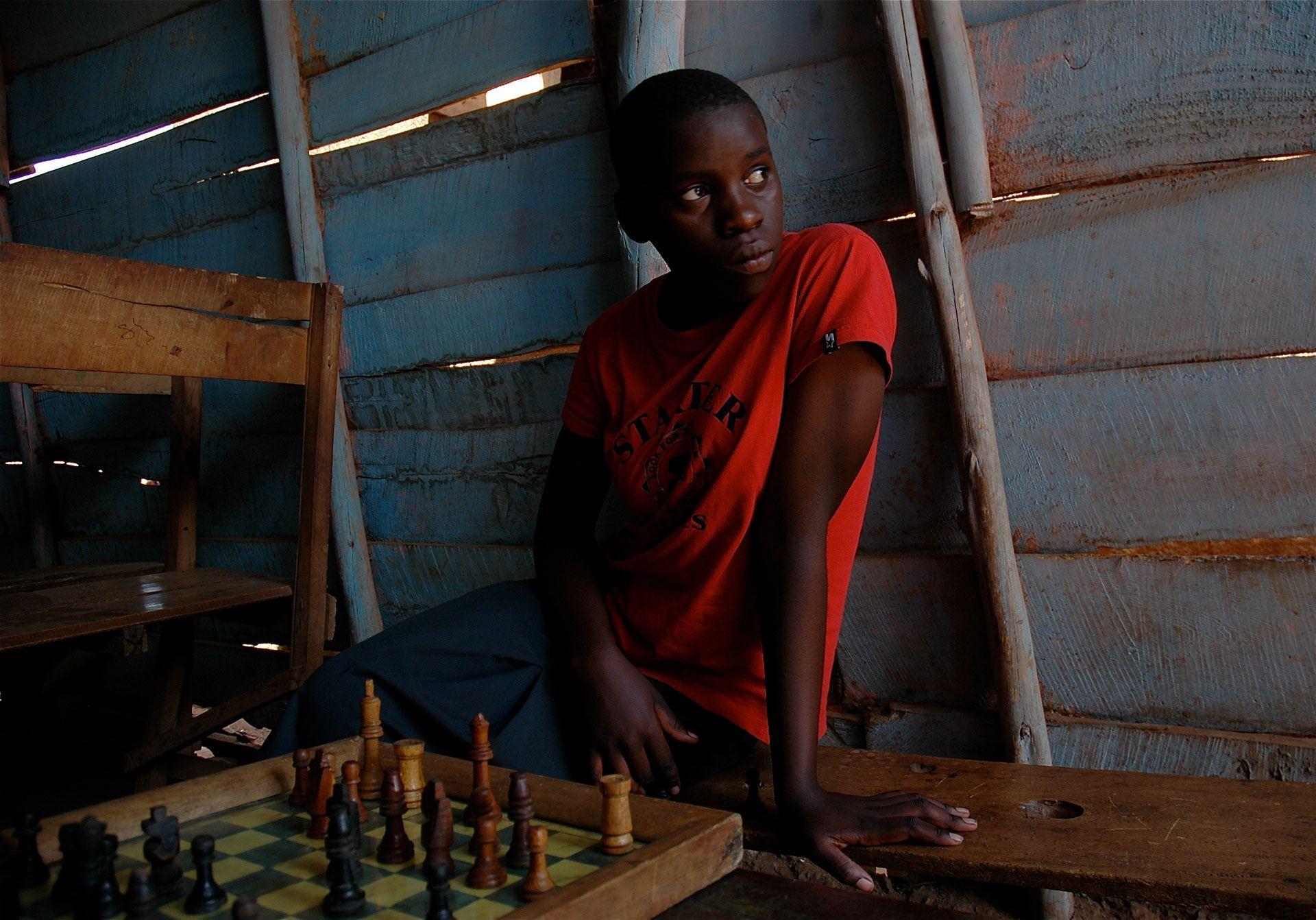 Phiona con el tablero en su tierra natal, Uganda, donde el juego la salvó de la pobreza extrema.