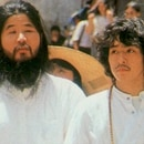 FILE - In this undated file photo, cult guru Shoko Asahara, left, of Aum Shinrikyo walks with Yoshihiro Inoue, then a close aid, in Tokyo. Thirteen Japanese cult members may be sent to the gallows any day now for a deadly 1995 gas attack on the Tokyo subway system and other crimes. Or they might not. Such is the secrecy that surrounds Japan's death penalty system. Tuesday, March 20, 2018, marks 23 years since members of the Aum Shinrikyo cult punctured plastic bags to release sarin nerve gas inside subway cars, sickening thousands and killing 13. Cult leader Shoko Asahara and a dozen followers have been sentenced to death for that and other crimes that killed 27 in all. (Kyodo News via AP, File)