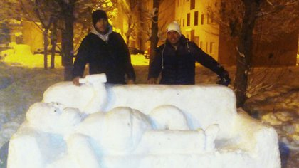 Alfredo y Maxi posan al lado de su impactante escultura de nieve.